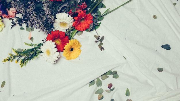 Primer plano de solidago gigantea y coloridas flores de gerbera sobre tela blanca