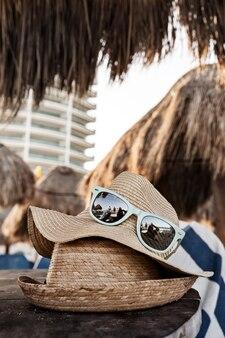 Primer plano de sombreros de paja de verano en la mesa de madera en la playa