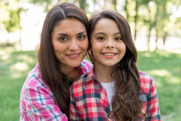 Primer plano de sonriente madre e hija de pie juntos en el parque