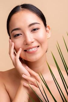Primer plano sonriente mujer asiática con hojas
