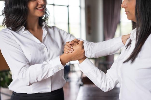 Primer plano de sonriente mujer de negocios apoyo colega en café.