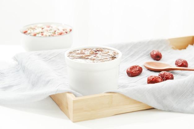 Primer plano de la sopa de cereales en un recipiente con una cuchara sobre un paño blanco en una bandeja de madera
