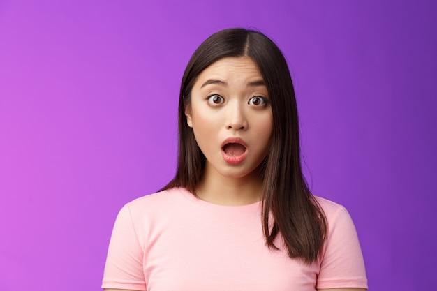 Primer plano sorprendido jadeando impresionado morena asiática caída mandíbula mirada cámara impresionado, muy sorprendido expresa total incredulidad, sin palabras escuchar asombrosas noticias, soporte fondo púrpura.