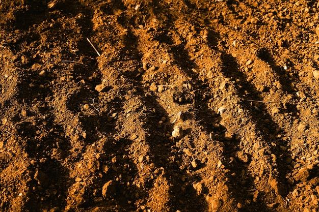 Primer plano de suelo de campo marrón con pequeñas piedras visibles
