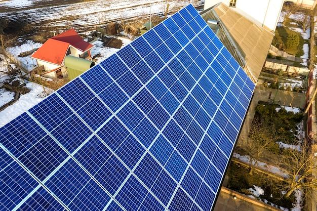 Primer plano de la superficie iluminada por el sol azul brillante sistema de paneles fotovoltaicos solares en el techo del edificio. concepto de producción de energía verde ecológica renovable.