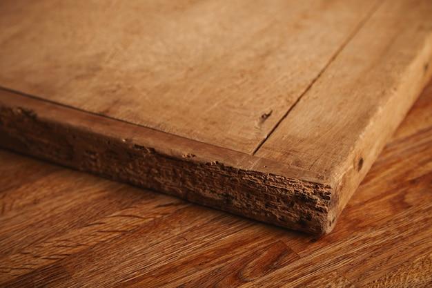 Primer plano de una tabla de cortar muy vieja y maltratada con cortes profundos, piezas que faltan acostado sobre una mesa de madera rústica