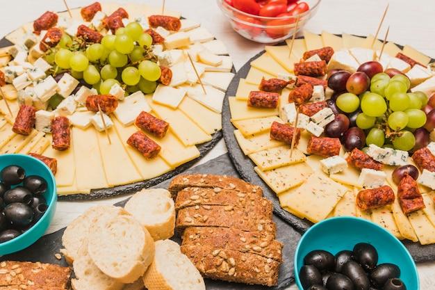 Primer plano de una tabla de quesos con uvas, aceitunas y salchichas ahumadas en tablero de pizarra
