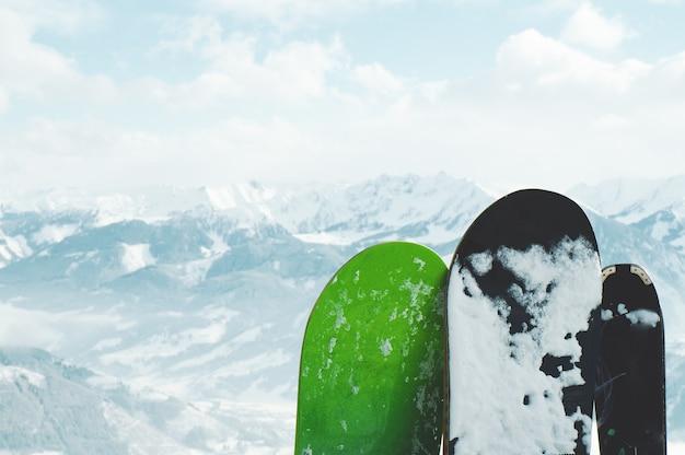 Primer plano de tablas de snowboard cubiertas de nieve en las montañas