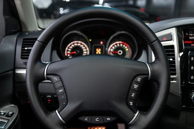Primer plano del tablero de instrumentos, velocímetro, tacómetro y volante. . interior del coche moderno