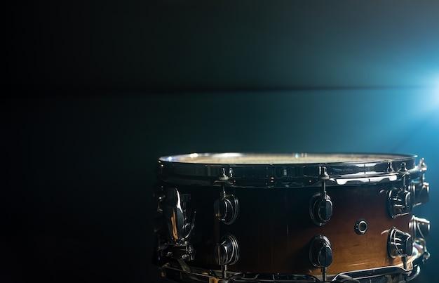 Primer plano de un tambor, instrumento de percusión sobre un fondo oscuro con una hermosa iluminación, copie el espacio.