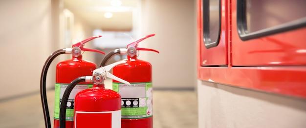 Primer plano del tanque de extintores rojo en la puerta de salida del edificio.