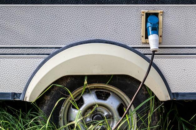 Primer plano de un tanque de gasolina con una pistola insertada para suministrar combustible a un automóvil viejo en la calle
