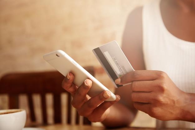 Primer plano de una tarjeta de crédito y un teléfono inteligente en manos de mujer