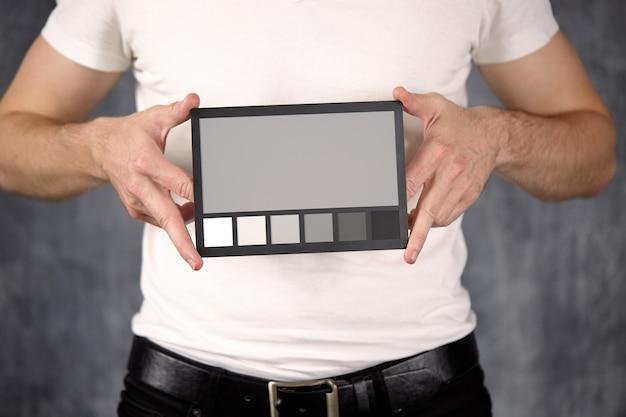 Primer plano de una tarjeta de verificación de color en las manos con tonos grises neutros