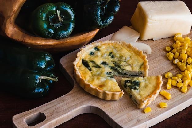Primer plano de tarta, queso y maíz en la tabla de cortar y pimientos verdes en la placa de madera