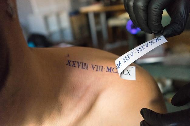 Primer plano de un tatuador colocando un diseño en el hombro de un cliente