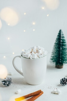Primer plano de una taza blanca con una bebida y malvaviscos con el telón de fondo de la decoración navideña sobre un fondo blanco.