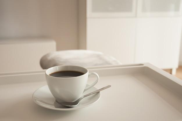 Primer plano de una taza de café caliente con un platillo y una cuchara en una bandeja en la cama por la mañana