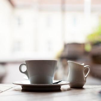 Primer plano de la taza de café de cerámica y la jarra de leche