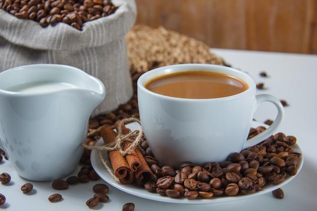 Primer plano de una taza de café con granos de café en un saco y platillo, leche, canela seca sobre salvamanteles y superficie blanca. horizontal