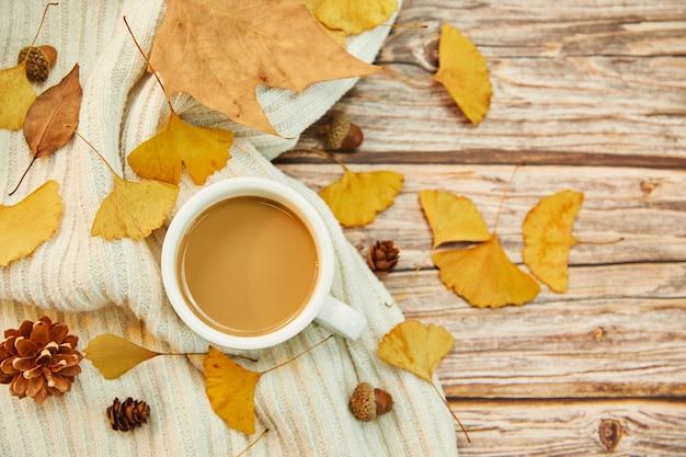 Primer plano de una taza de café y hojas de otoño sobre fondo de madera