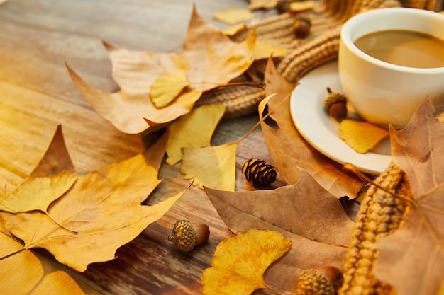 Primer plano de una taza de café y hojas de otoño sobre la superficie de madera