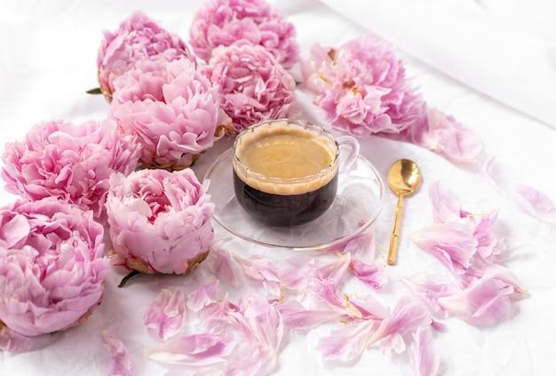 Primer plano de una taza de café instantáneo en un platillo sobre la mesa con peonías rosas en él
