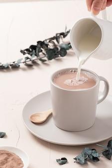 Primer plano de una taza de café con leche y algunas decoraciones sobre una mesa blanca