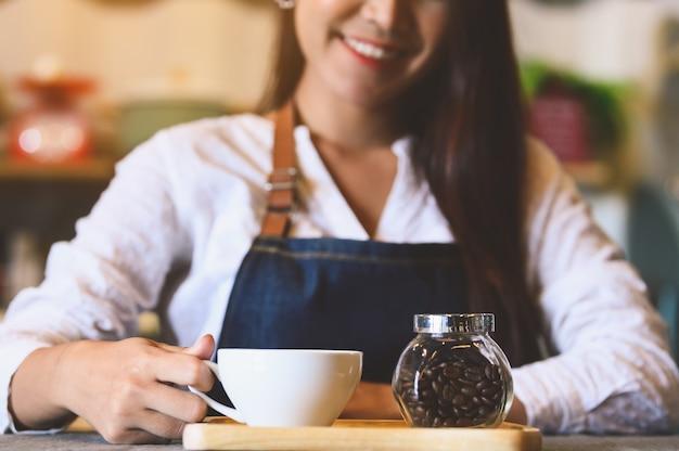 Primer plano de una taza de café con leche con hermosa mujer asiática barista