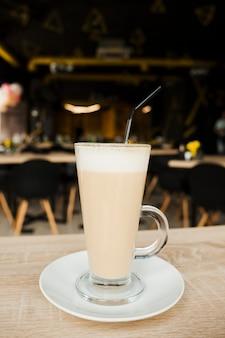 Primer plano de la taza de café con leche con paja y platillo en el escritorio de madera