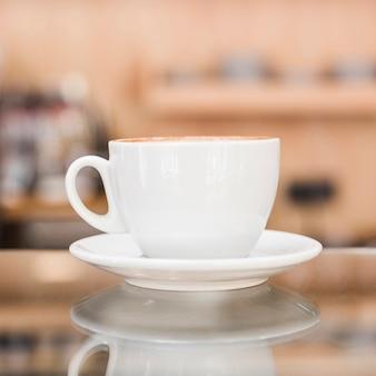 Primer plano de la taza de café con leche en la tienda de café