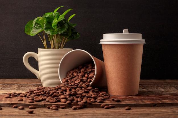 Primer plano de una taza de café de papel artesanal en blanco sobre la mesa de madera. espacio para tu publicidad. maqueta horizontal