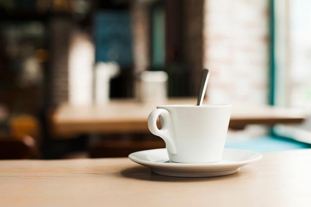 Primer plano de la taza de café con el platillo en la mesa de madera en la cafetería