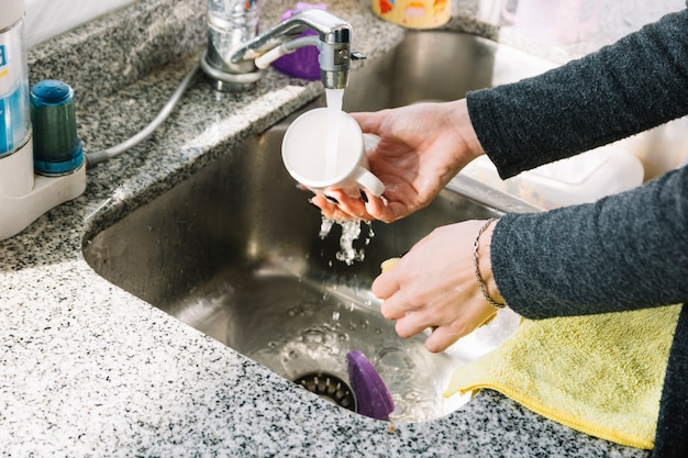 Primer plano de la taza de lavado de manos de una mujer en el fregadero de la cocina