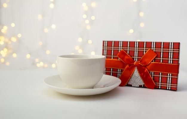 Primer plano de una taza con un platillo y una caja de regalo roja sobre un fondo blanco con un bokeh con un lugar para el texto