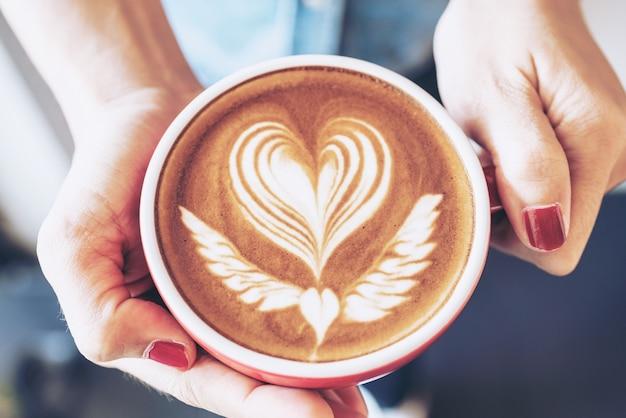 Primer plano de una taza roja de arte latte de café en mano de mujer en cafetería cafetería