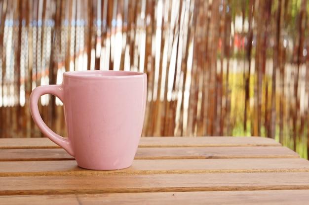 Primer plano de una taza rosa sobre una mesa de madera