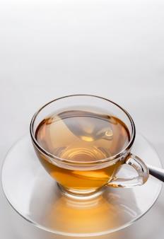 Primer plano de una taza de té caliente recién hecho en un vaso sobre la superficie blanca con espacio de copia.