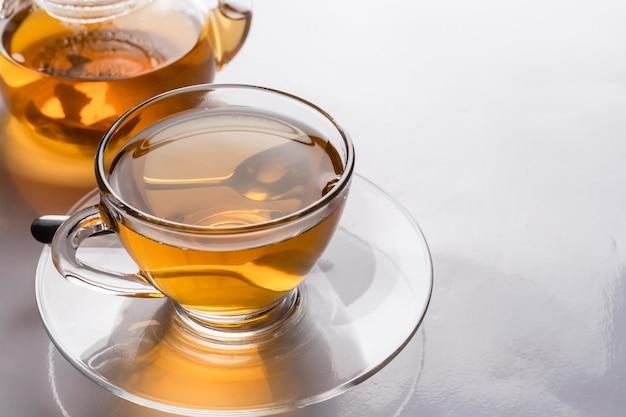 Primer plano una taza de té caliente recién hecho en vidrio transparente y tetera sobre la mesa con reflejo.