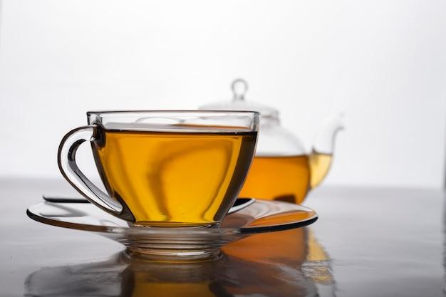 Primer plano de una taza de té caliente recién hecho en vidrio transparente y tetera sobre la mesa.