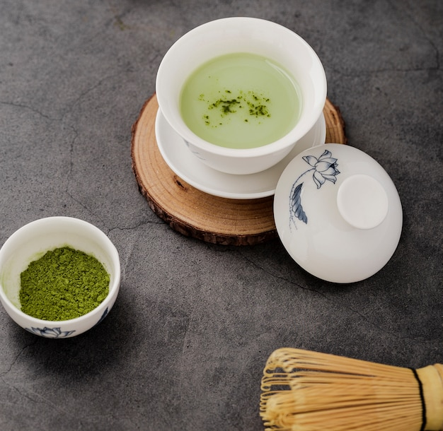 Primer plano de la taza de té matcha con batidor de bambú