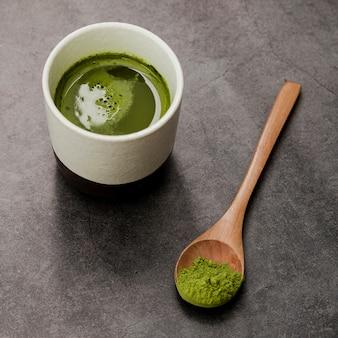 Primer plano de la taza de té matcha con cuchara de madera