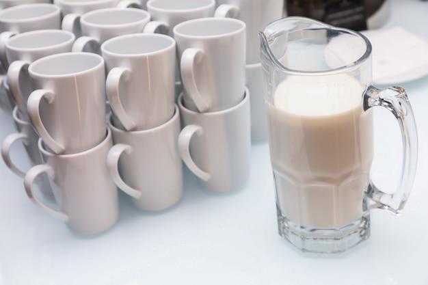 Primer plano de tazas blancas y una jarra de leche sobre una mesa de luz