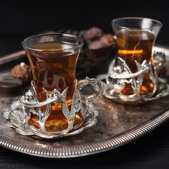 Primer plano de tazas de té en bandeja de plata