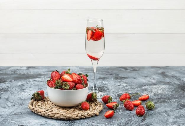 Primer plano de un tazón de fresas en mantel de mimbre redondo con un vaso de bebida en mármol azul oscuro y superficie de tablero de madera blanca. horizontal