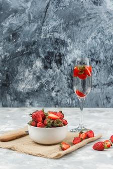 Primer plano de un tazón de fresas en un trozo de saco con un vaso de bebida en la superficie de mármol blanco y azul oscuro. vertical