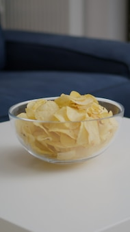 Primer plano de un tazón de patatas fritas chatarra puesto en la mesa de madera en la sala de fiestas vacía