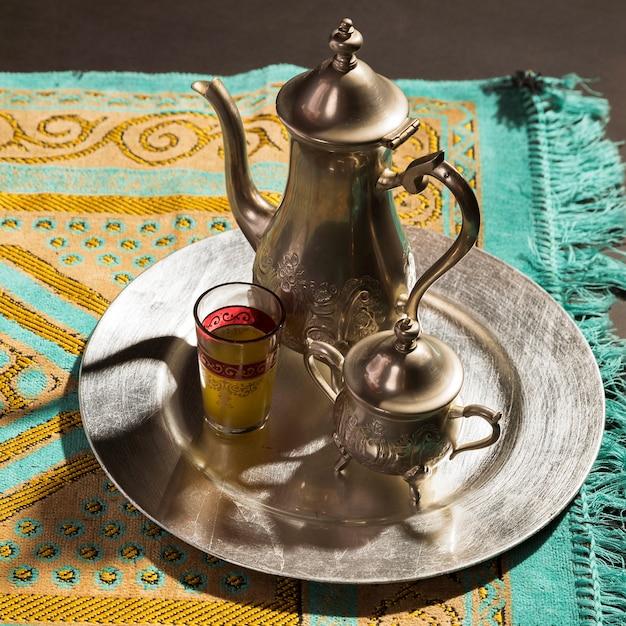 Primer plano de té caliente árabe tradicional en la alfombra de oración
