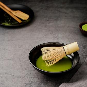 Primer plano de té matcha en un tazón con batidor de bambú