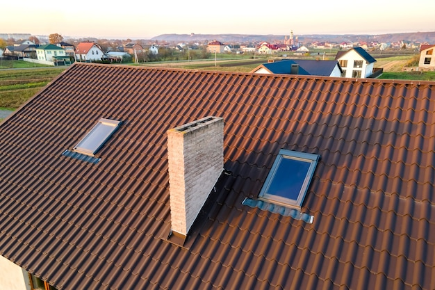 Primer plano del techo de ladrillo de la casa con cubierta de tejas amarillas y ventanas de vidrio del ático.